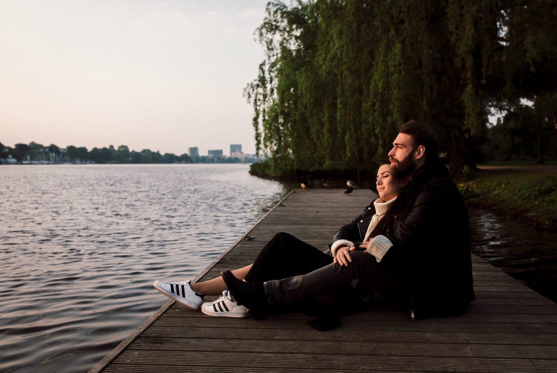das Paar sitzt gemeinsam auf einem Steg an der Alster und beobachtet den Sonnenaufgang