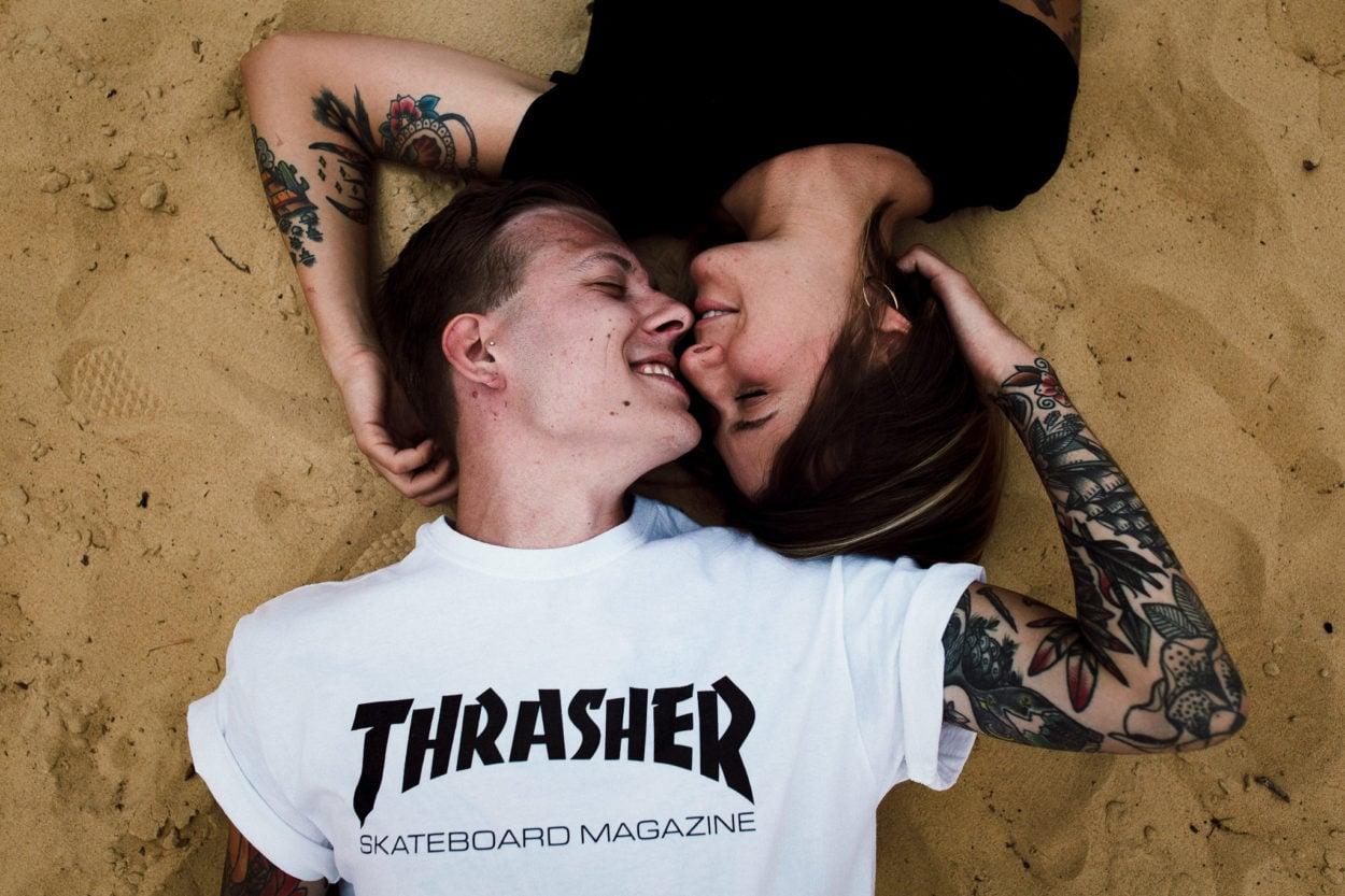 Trasher und im Sand liegendes Paar