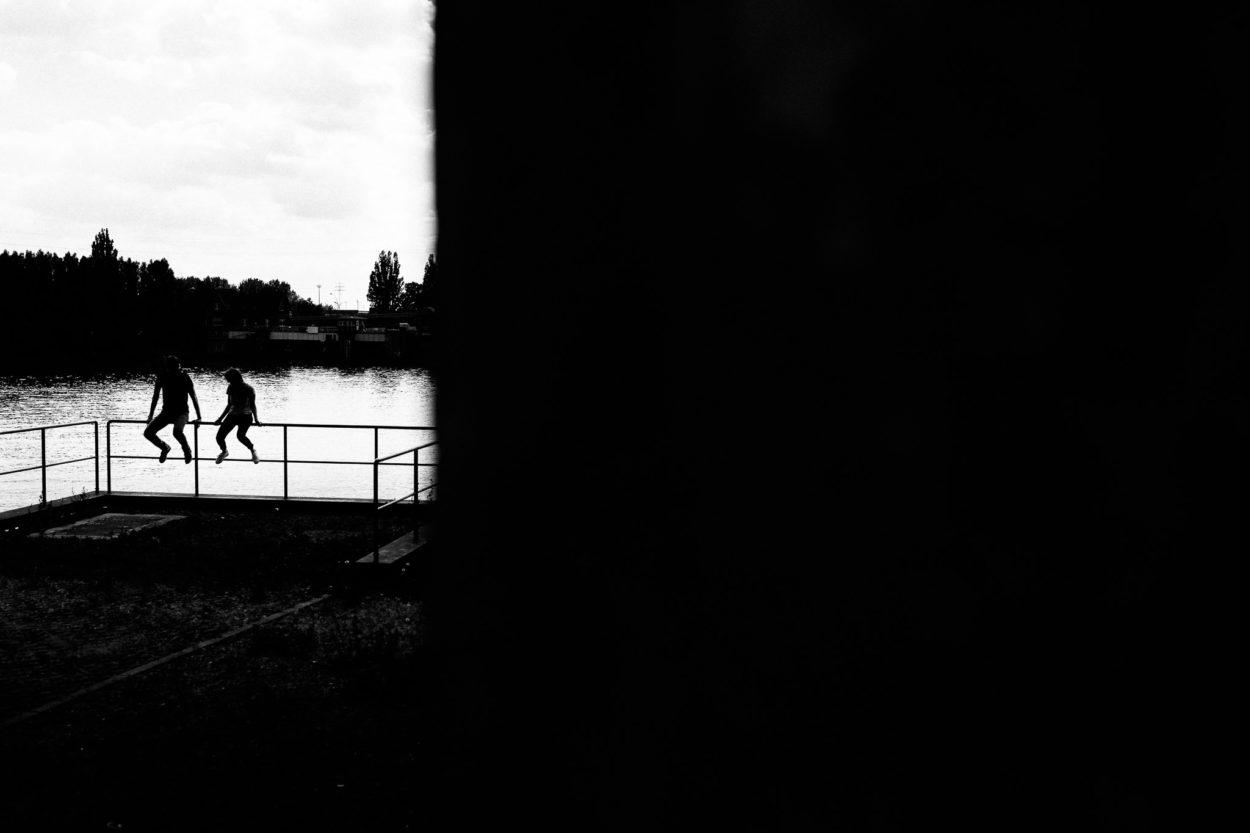 Das Paar sitzt auf einem Geländer an der Elbe. Das Bild ist schwarz weiß