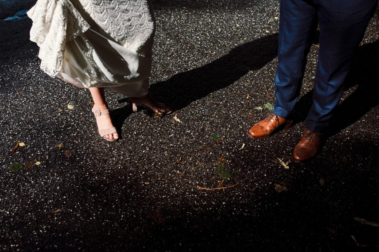 Die Schuhe des Hochzeitspaares werden von der Sonne angestrahlt