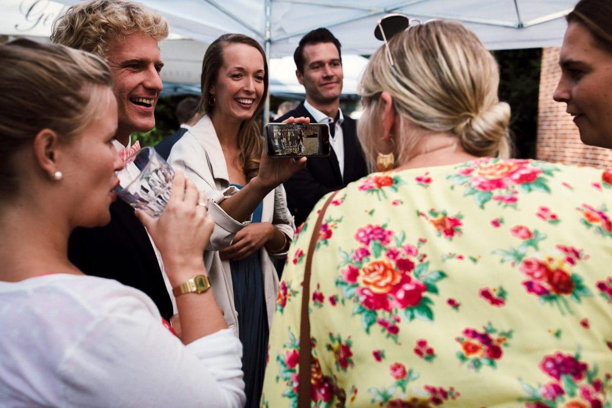 Die Gäste betrachten Bilder auf ihrem Smartphone