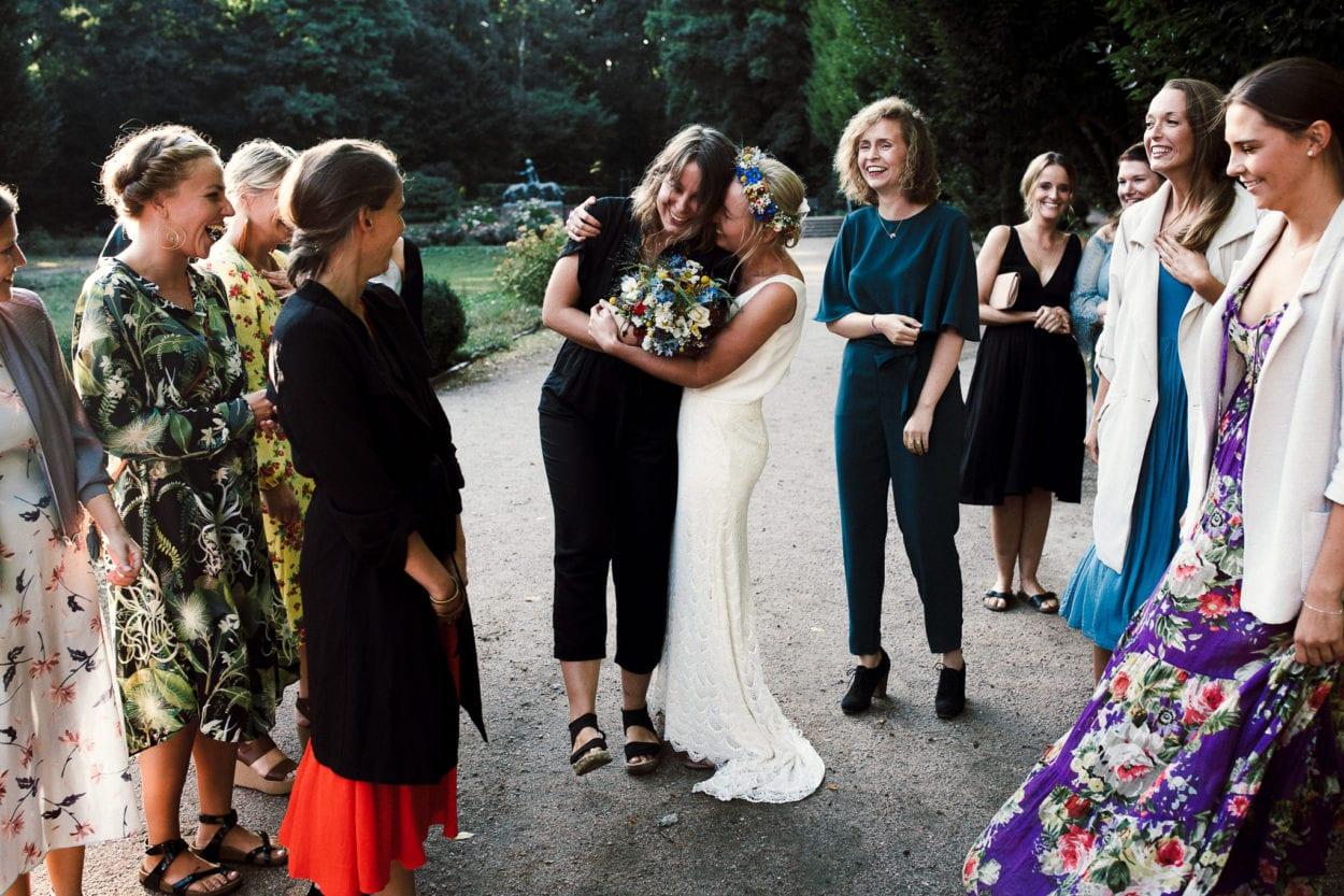 fröhliche Umarmung nach dem Brautstrauß Wurf