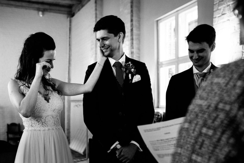 Die weinende Braut streichelt liebevoll ihren Bräutigam - Hochzeitsfotograf Lüneburg