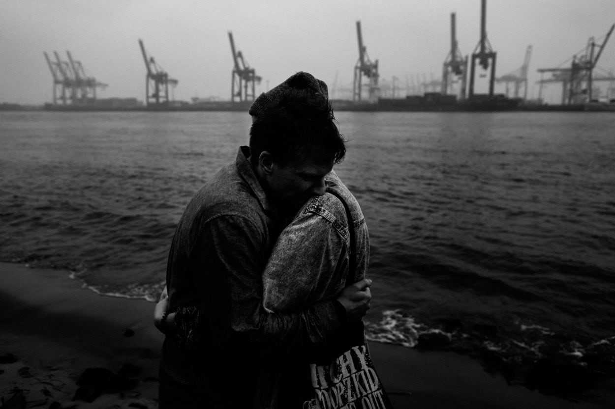 Paar am Elbstrand in schwarz weiß mit den Kränen der Industrie im Hintergrund