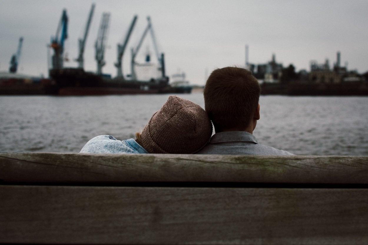 Paar auf einer Bank mit Blick auf den Hafen