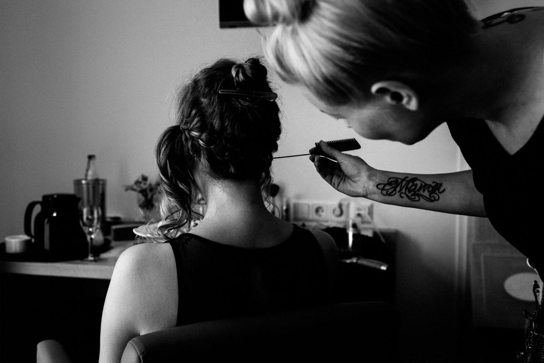 Braut wird gestyled und auf dem Arm der MakeUp Artistin steht Mama