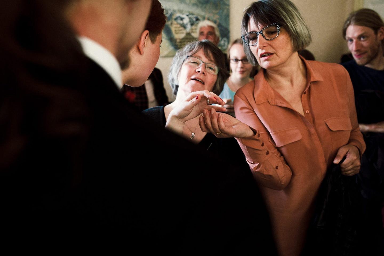 Braut und Gäste betrachten den Ring nach der Trauung