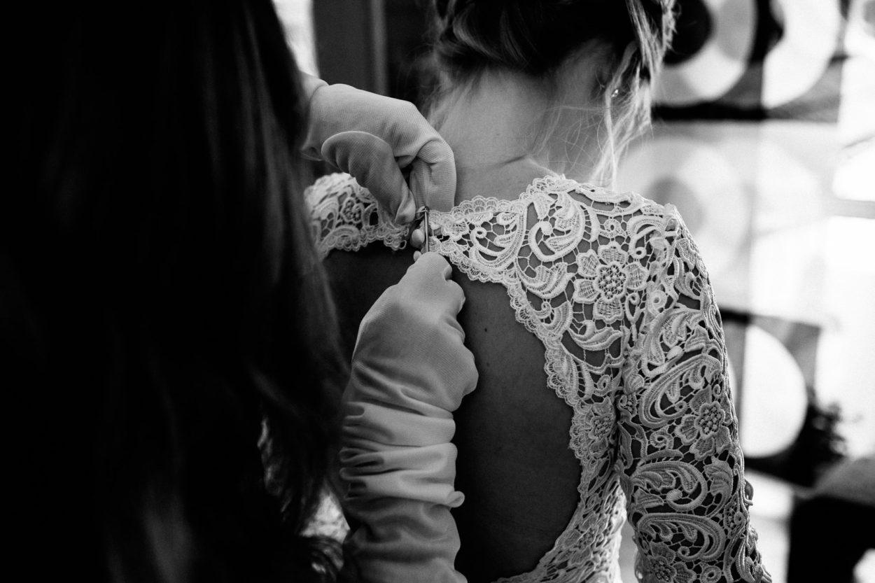 die letzten Knöpfe werden am Hochzeitskleid zugezogen