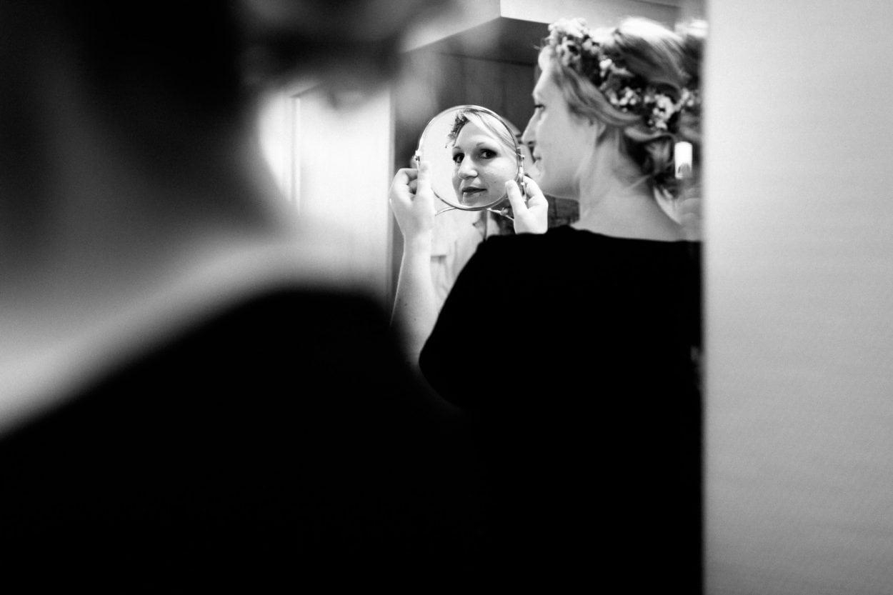 Die Braut betrachtet sich im Spiegel
