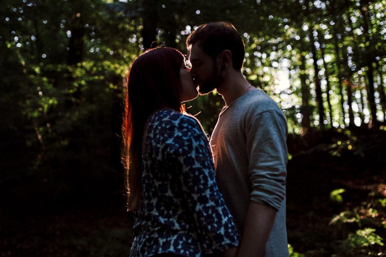 küssendes Paar wird im Wald von der Sonne angestrahlt
