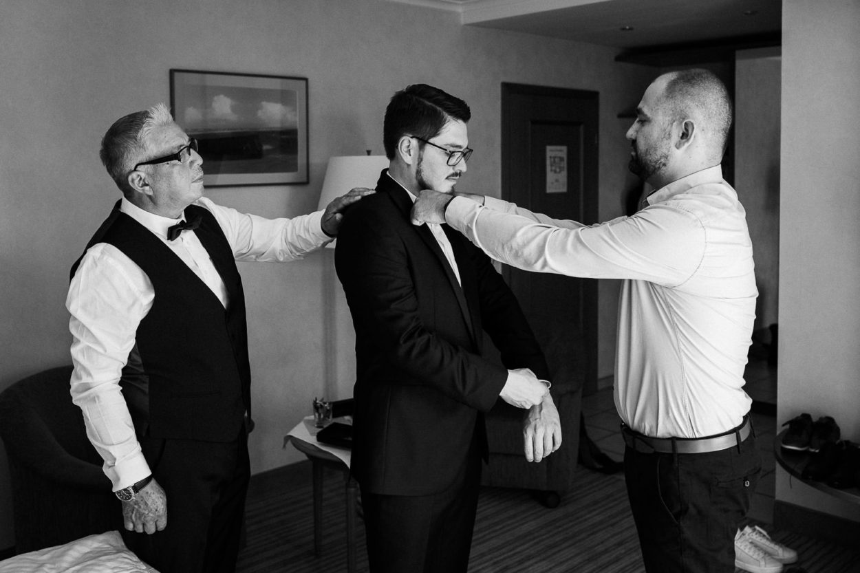 Brautvater und Trauzeuge helfen dem Bräutigam beim ankleiden