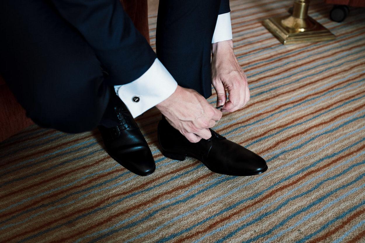 Hände beim Schuhe zubinden.