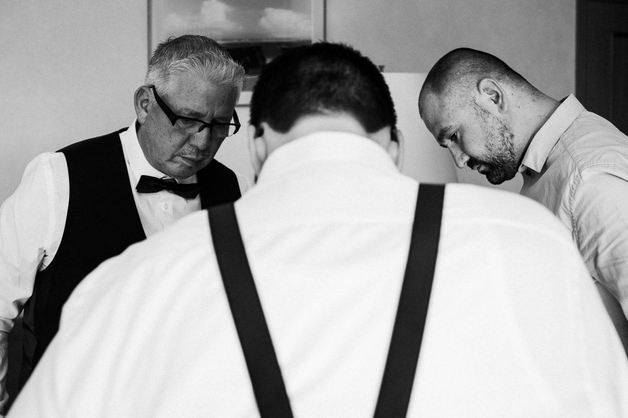 Brautvater und Trauzeuge betrachten den Bräutigam