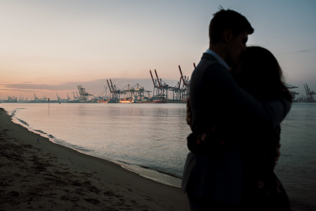 Ein Paar im Vordergrund und der Hafen in Hamburg im Hintergrund