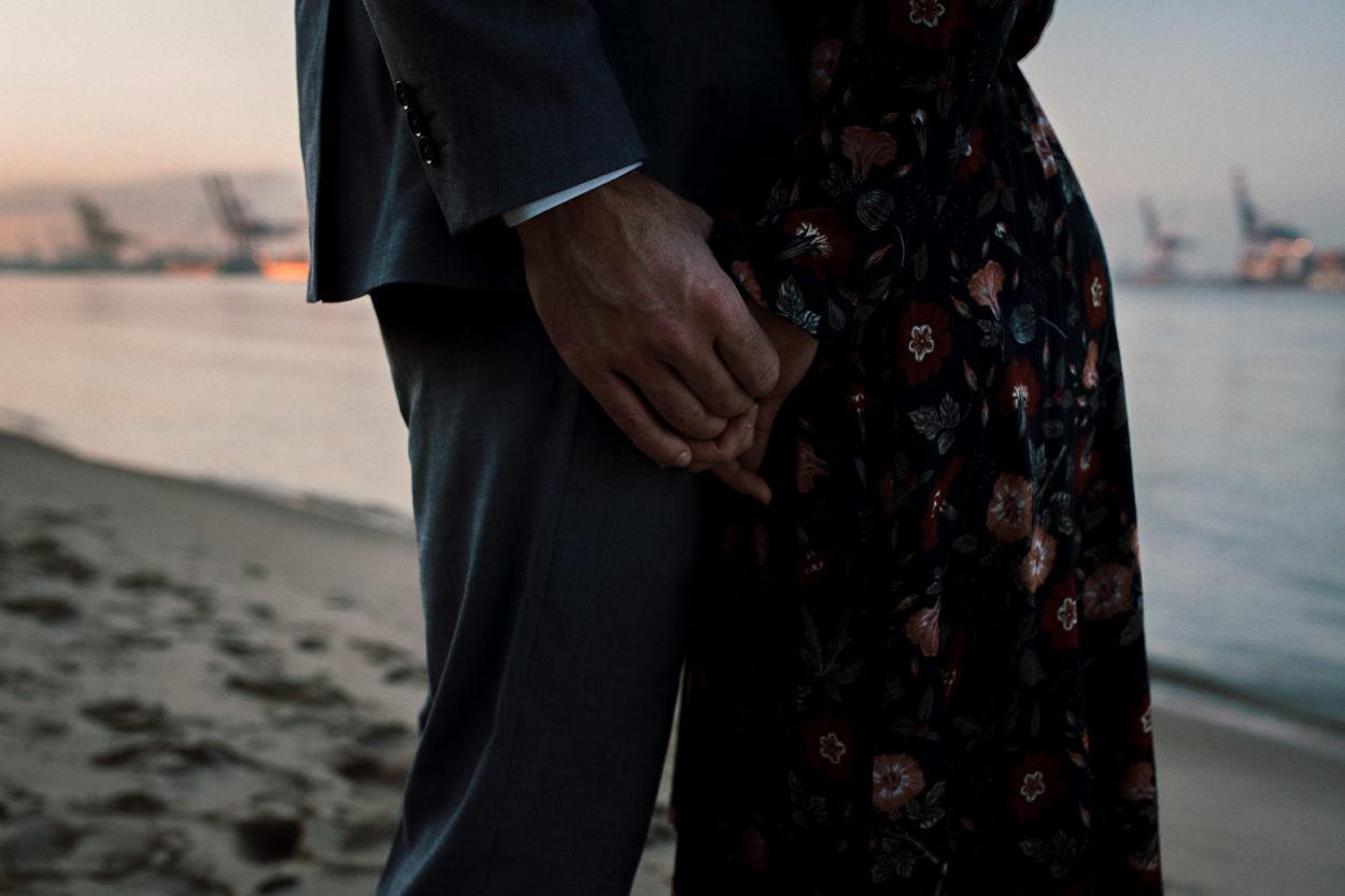 Ein Paar hält Hände am Elbstrand