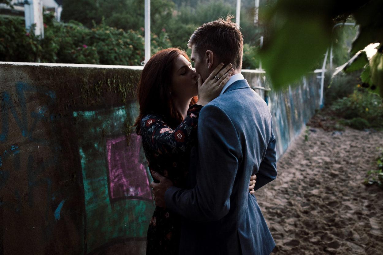 ein küssendes Paar vor einer Mauer